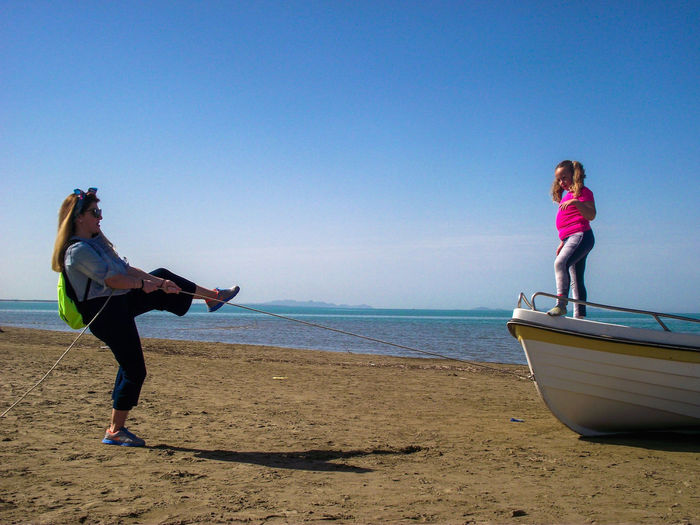 Mother Pulling Boat With Daughter At Beach Against Blue Sky