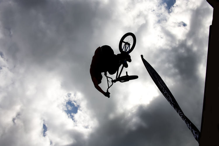 Silhouette of person jumping with bicycle