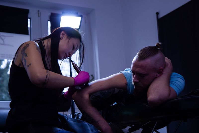 Side View Of Artist Tattooing Mid Adult Man In Workshop