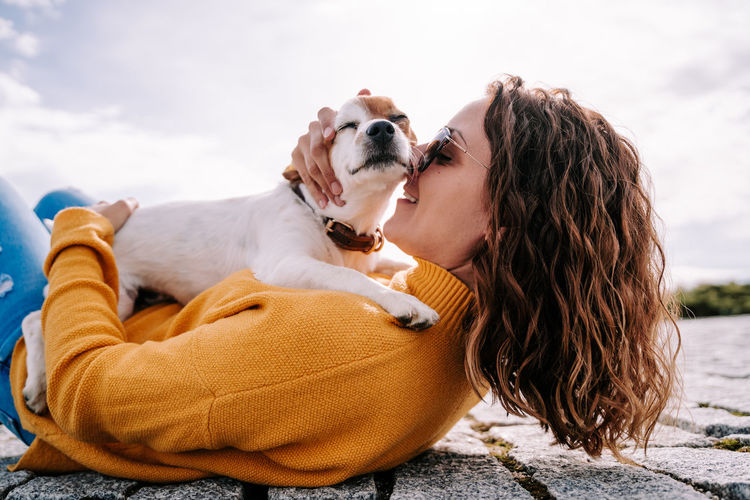 Woman lying down on floor with dog outdoors