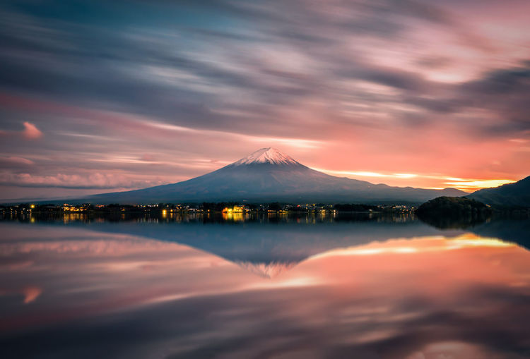 Scenic view of lake and mt fuji against cloudy sky during sunset