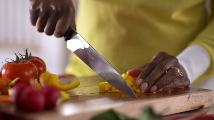 Midsection Of Person Chopping Vegetable On Cutting Board In Kitchen