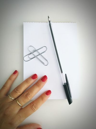 Close-up of hand holding paper against white background