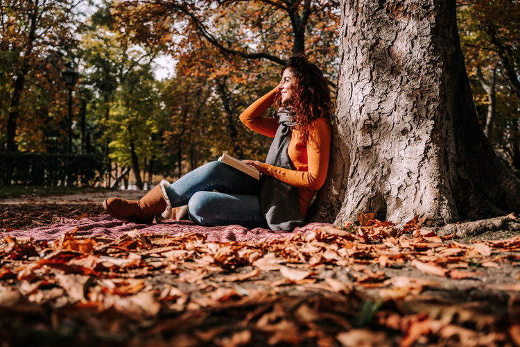 Woman sitting on tree trunk during autumn