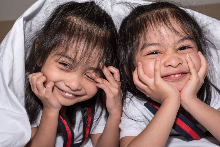 Portrait of smiling sisters at home