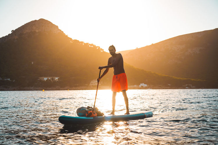 Full length of man standing on paddleboard in lake