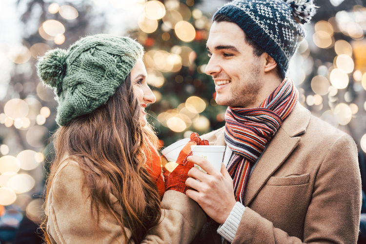 Woman and man enjoying mulled wine on a Christmas market Christmas Market Couple Happy Lights Love Loving Woman Christmas christmas tree Clothing Emotion Happiness Mammal Men Mulled Wine Scarf Winter Women