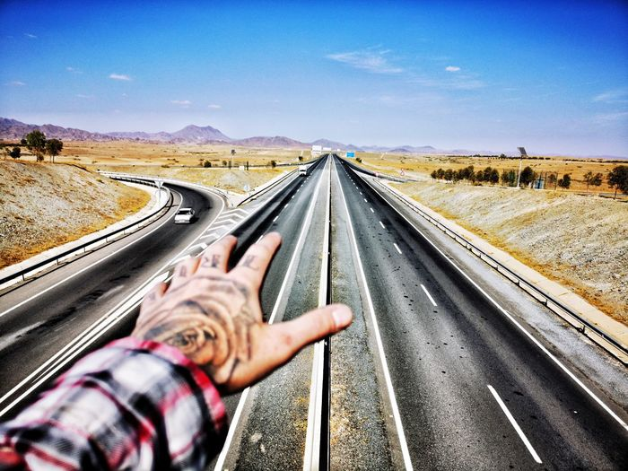 Cropped tattooed hand of man gesturing on road against sky