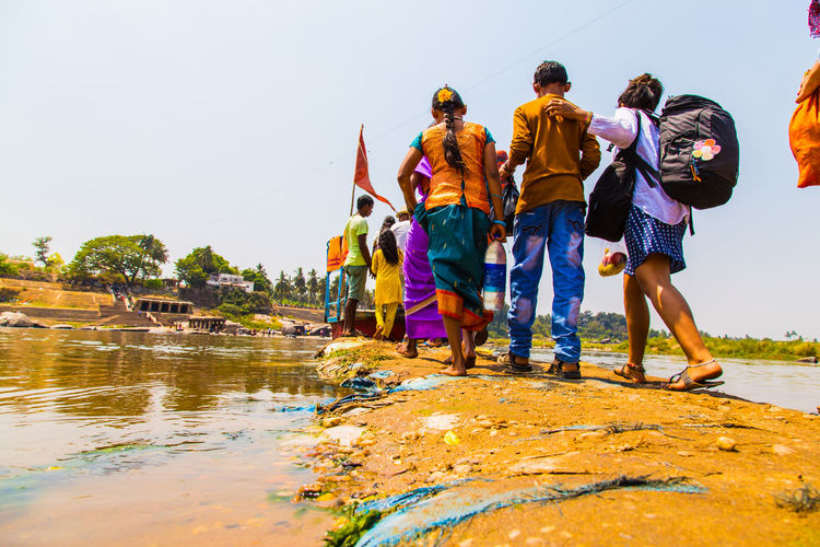 People crossing the river, Hampi Crossing Rivers Feet Walking Ground Level View Group Of People Hampi  Hindu India Indian Culture  Indian Family Indian People Karnataka Men Outdoors People Religion River Shiva Traditional Clothing Travel Travel Destinations Unesco Unesco World Heritage Walk Walking Water
