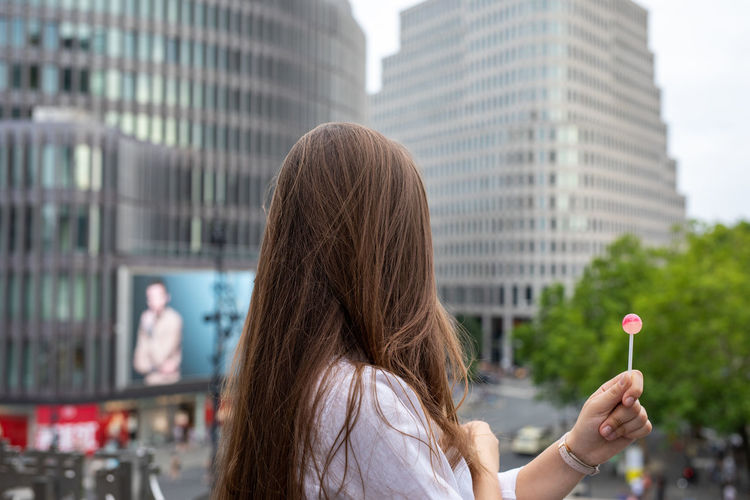 Side view of young woman holding lollipop by buildings in city