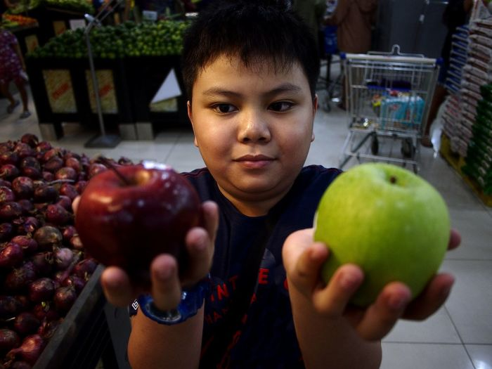 High Angle View Of Boy Holding Apples While Standing In Supermarket