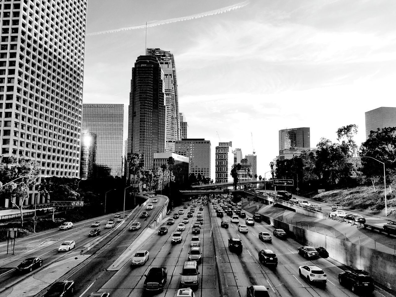 city, transportation, skyscraper, architecture, land vehicle, building exterior, built structure, road, car, street, mode of transport, city life, tall, outdoors, sky, day, urban skyline, modern, cityscape, tree, no people