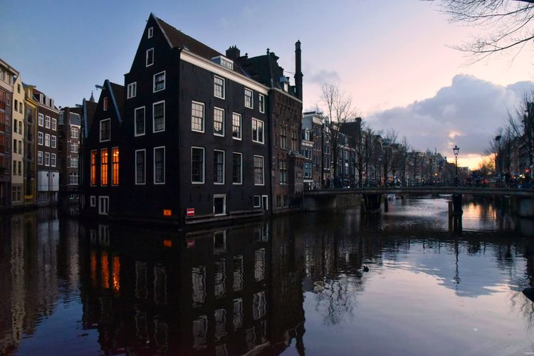 When in Amsterdam... Settlement House Wintertime Sunset Urban Landscape Travel Destinations Eye4photography  EyeEm Gallery Residential District Amsterdamcity Amsterdam Canal EyeEm Malephotographerofthemonth Reflection Winter Cityscape Travel Photography Destination City Water Cityscape Symmetry Reflection Sky Architecture Building Exterior Canal Arch Bridge Old Town Townhouse