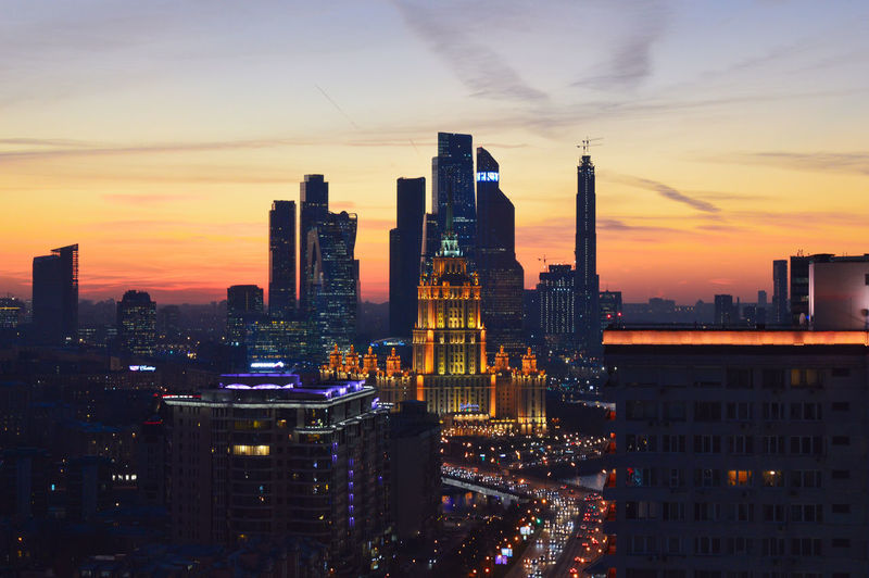 Illuminated buildings in city against sky during sunset