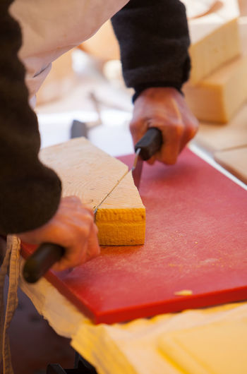 Midsection of man cutting cheese on table