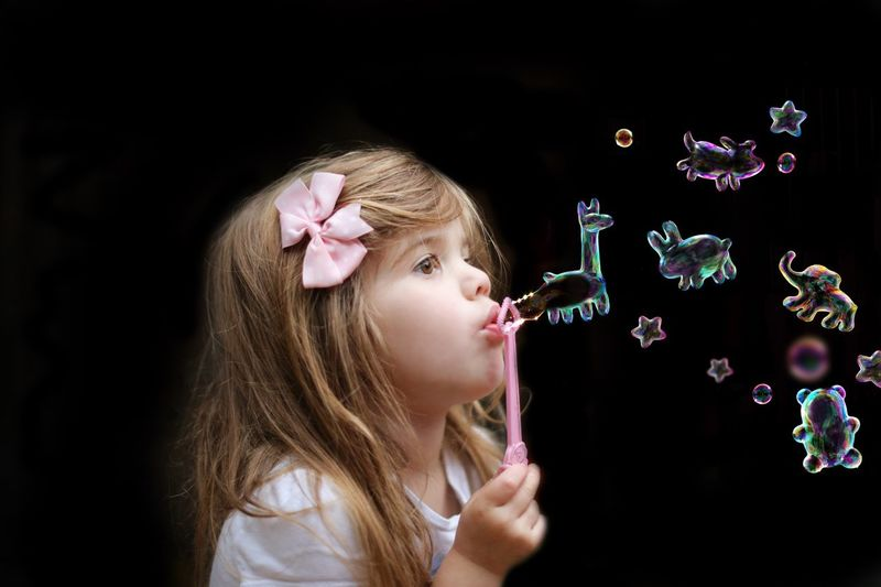 Side view of cute girl blowing animal shape bubbles against black background