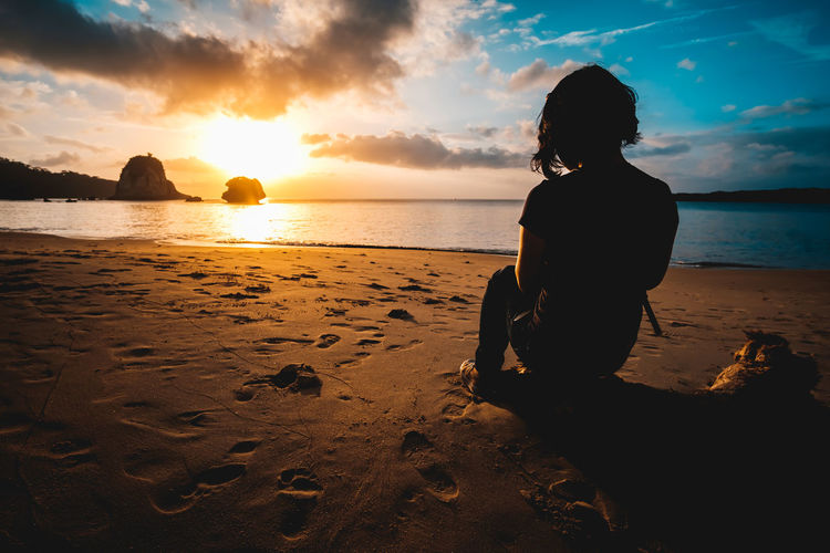 Rear view of woman looking at sea against sunset sky at a beach