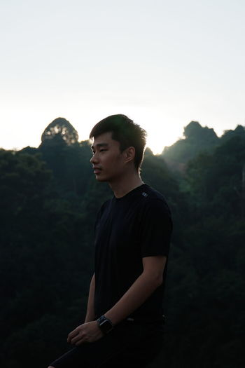 Young man looking away against mountains