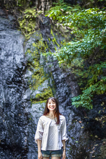 Portrait of woman smiling while standing against wet rock