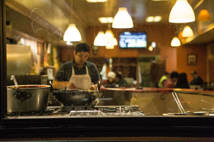 a cook at a restaurant seen from outside at night Preparing Food Kitchen Utensil Lifestyles Illuminated Indoors  Real People Restaurant Worker Restaurant Pots Night Kitchen Cozy Cooking Cook