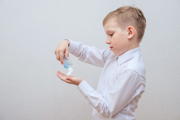 Boy looking away while standing against white wall