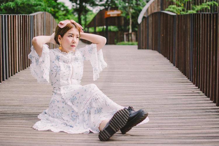 Full length of woman sitting on footbridge at park