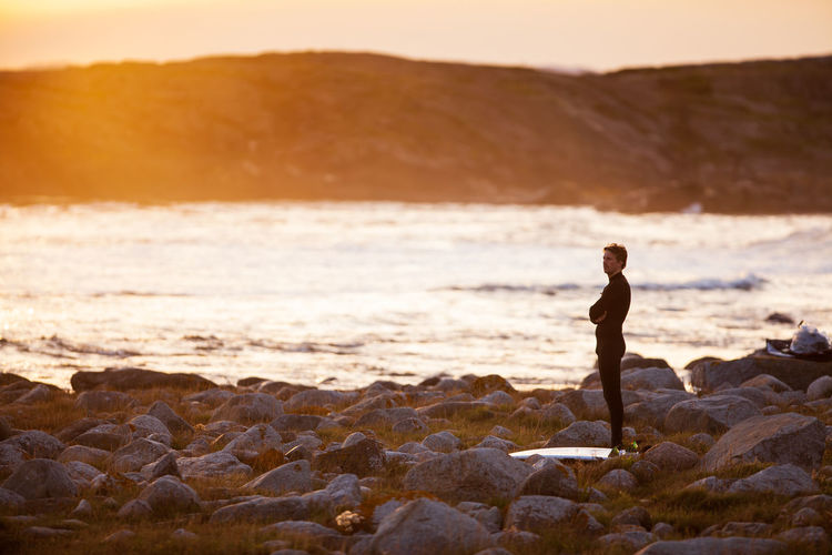 Man standing on rock at beach against sky during sunset