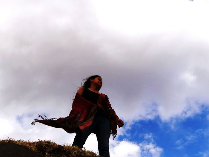 Low angle view of woman standing on cliff against cloudy sky
