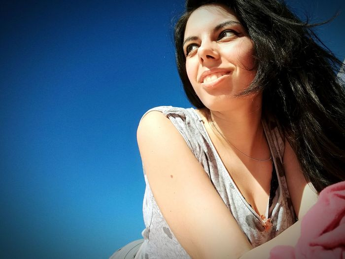 Low Angle View Of Thoughtful Woman Lying Against Clear Blue Sky