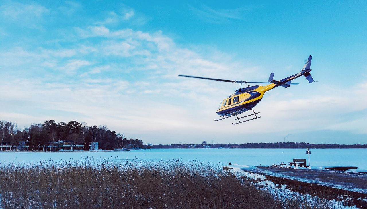 Helicopter flying over frozen lake against sky