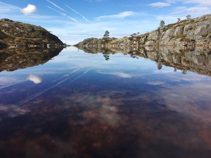 Reflection of rocks in lake against sky