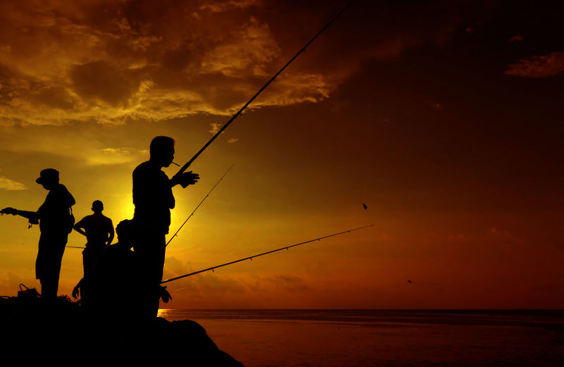 Silhouette people fishing in sea against sky during sunset