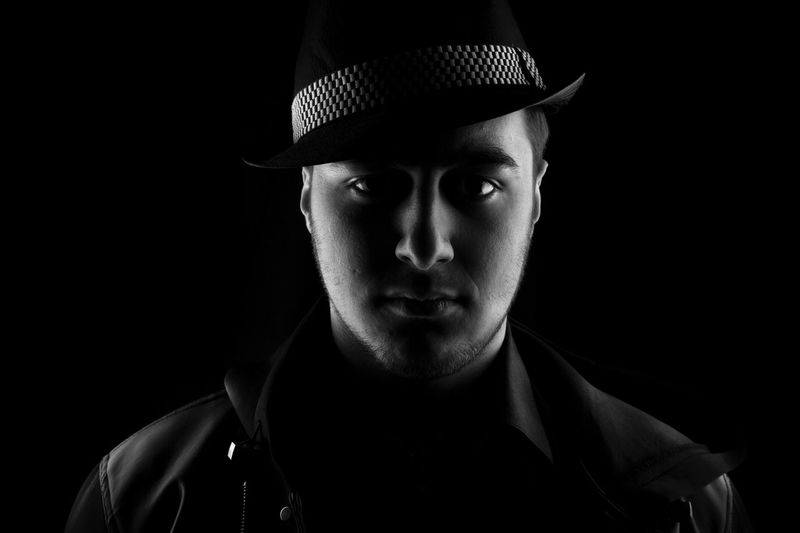 Close-up portrait of young man wearing hat over black background