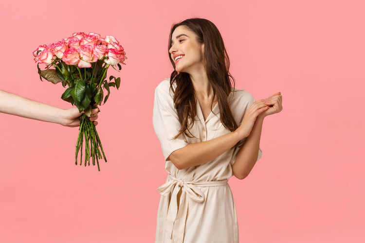 Woman with pink roses against white background