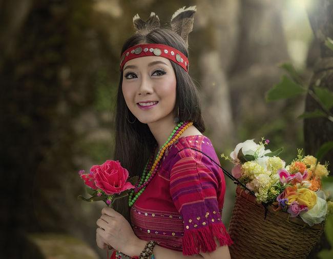Portrait of smiling woman holding flower bouquet