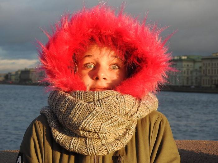 Portrait of girl in red fur coat against lake