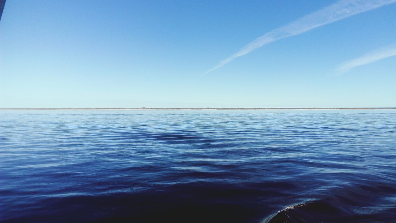 beauty in nature, scenics, sea, blue, tranquility, tranquil scene, nature, water, rippled, no people, sky, idyllic, outdoors, horizon over water, day, clear sky, vapor trail