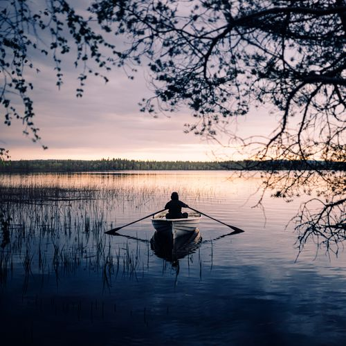 Silhouette of man rowing boat on lake during sunset