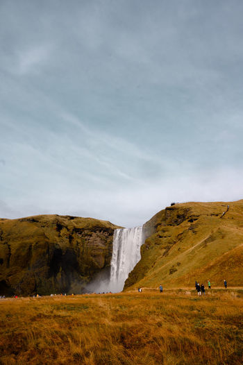 Scenic view of waterfall on land against sky