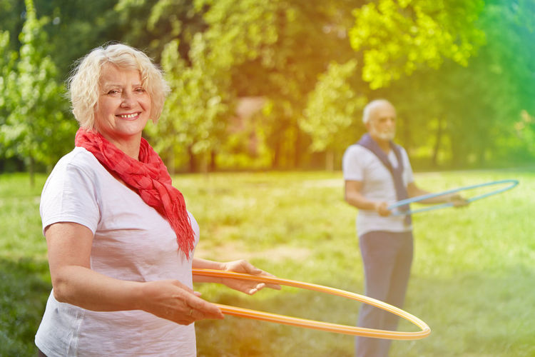 Portrait Of Smiling Senior Woman Spinning Plastic Hoop While Standing At Public Park