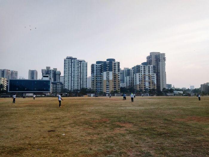 People in field against buildings in city