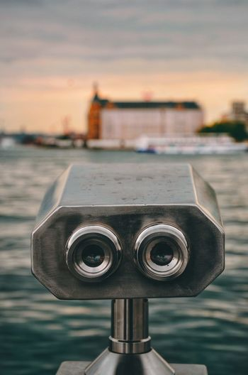 Close-up of coin-operated binoculars against bay during sunset