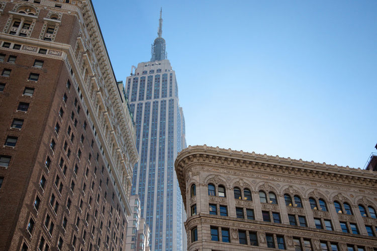 Low angle view of empire state building at flatiron building against clear sky