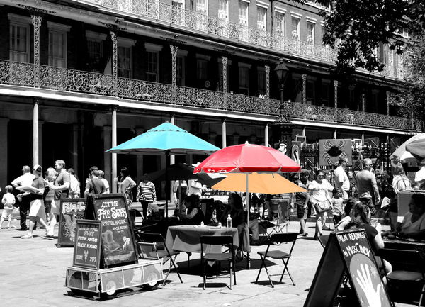 A street scene in Jackson square in New Orleans in black and white, with historic buildings and iron railings, fortune teller tables and market umbrellas in colors of aqua blue, red and yellow. Aqua Architecture Art Fair Black And White Blue Brick Building City Life Fortune Telling Gold Ironwork  Jackson Square Market Market Umbrellas New Orleans Outdoors Red Street Scene