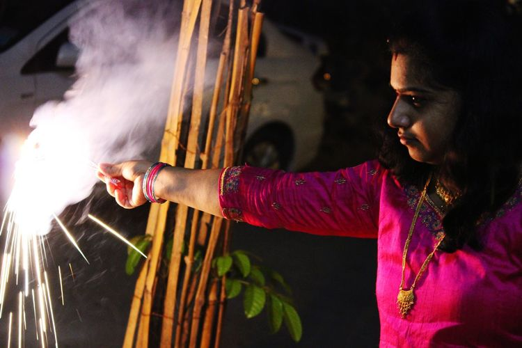Mid Adult Woman Playing With Sparklers At Night