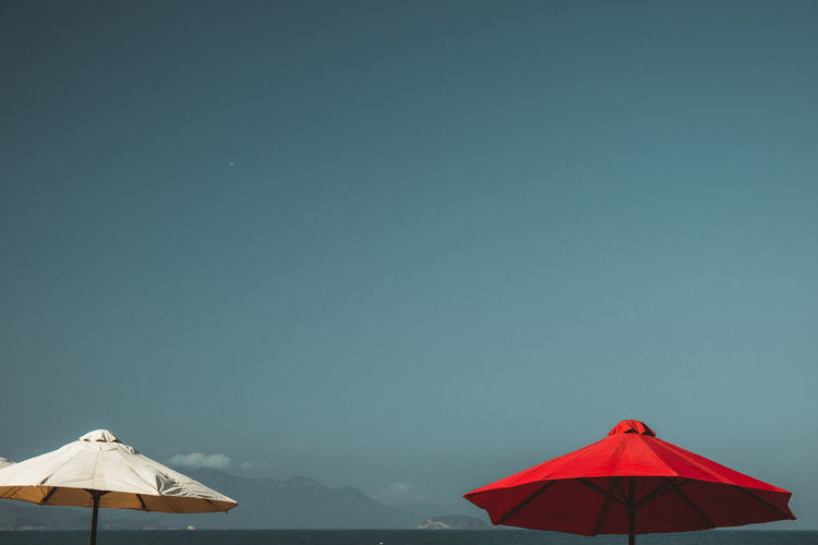 Parasols against clear blue sky during summer