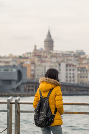 Girl in Yellow & the Galata Tower Architecture Building Exterior City City Life Cityscape Cityscapes Eminönü Famous Place Focus On Foreground Galata Galata Tower Istanbul Istanbul Turkey 43 Golden Moments The OO Mission Fine Art Photography Rainy Days Rear View Seaside Selective Focus Original Experiences The Portraitist - 2016 EyeEm Awards Travel Destinations Yellow My Year My View