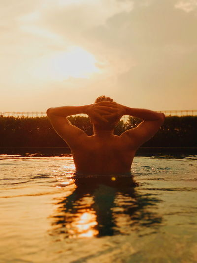 Midsection of woman in sea against sky during sunset