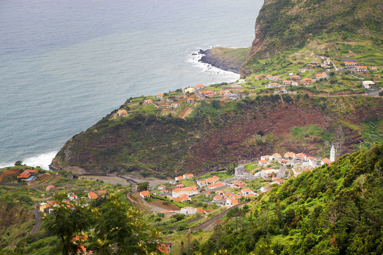 High Angle View Of Buildings On Mountain By Sea