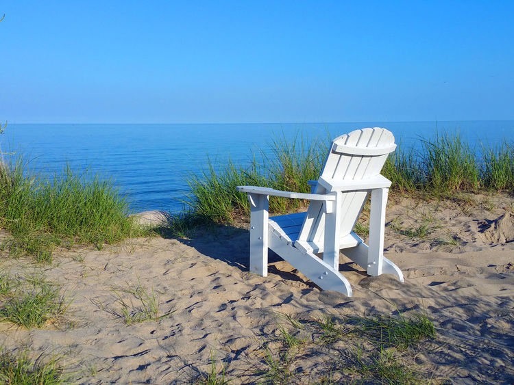Beach chairs overlooking the water Absence Beach Chairs Beauty In Nature Blue Calm Clear Sky Coastline Day Empty Grass Horizon Over Water Nature No People Non-urban Scene Ocean One Outdoors Remote Scenics Sea Shore The Way Forward Tranquil Scene Tranquility Water